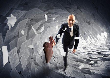 businessman runs from a paperwork