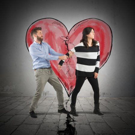 Photo for Man pulling a woman with broken heart in background - Royalty Free Image