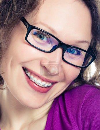 Photo pour Belle fille souriante portant des bretelles sur un fond blanc - image libre de droit