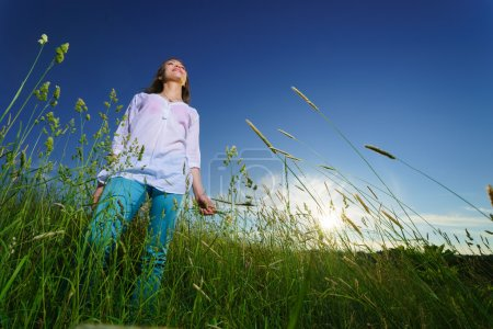Photo pour Jeune femme marche sur le champ vert - image libre de droit