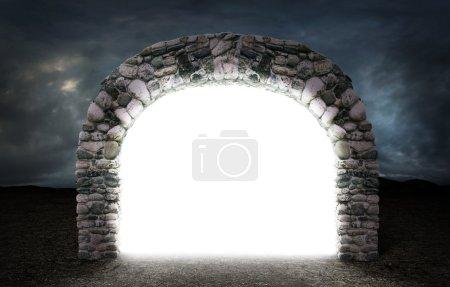 Photo pour Concept de dimension différente. Portail mystérieux blanc vers un autre espace à travers une arche de pierre avec un désert sombre à l'extérieur . - image libre de droit