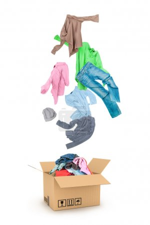 clothes falling into the cardboard box isolated on white