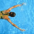 Young woman swimming in a blue water of swimming p...