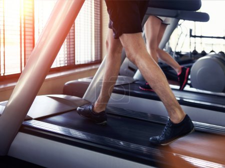Healthy man and woman running on a treadmill