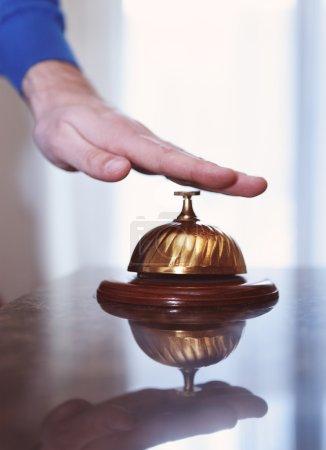 Photo pour Main d'un homme utilisant une cloche d'hôtel dans un style rétro - image libre de droit