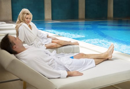 Couple relaxing by the poolside wearing toweling robes