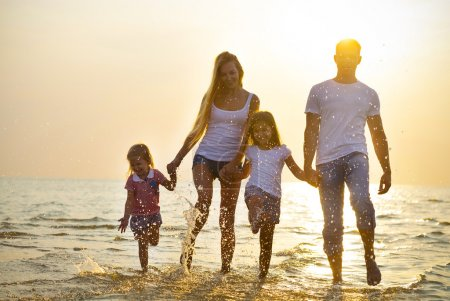 Photo for Happy young family having fun running on beach at sunset. Toned photo. Family traveling concept. No effects - real sun - Royalty Free Image