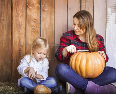 Mother and her little daughter carving Halloween pumpkins