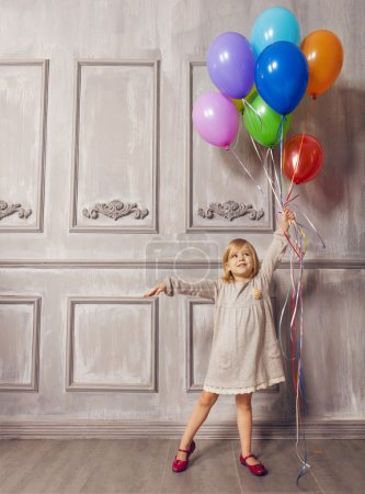 Photo for Cute little girl in retro style holding balloons over wall background - Royalty Free Image