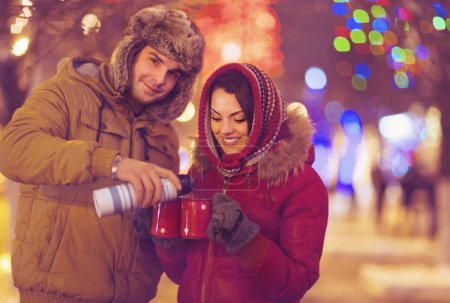 Happy young couple drinking tea on blurred lights background