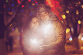 Young couple with Bengal light looking at camera outside