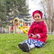 Little girl sitting on green grass on playground i...