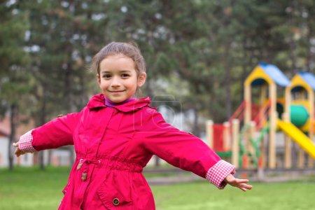 Photo pour Le plaisir de la petite fille sur l'aire de jeux au printemps. Enfant en vêtements rouges dans le parc pour enfants - image libre de droit