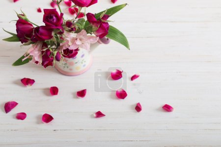 bouquet of bright flowers in watering can on wooden background