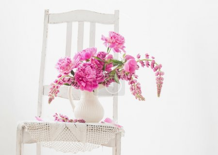 Peony flowers in a  vase on vintage chair