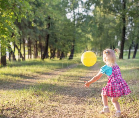 child playing a ball in the park