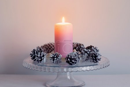 Christmas candle burning bright with  pine cones