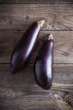 purple eggplants on wooden background