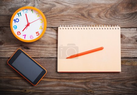 Smart phone, alarm clock and notebook on wooden background