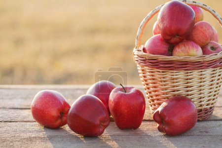Photo for Red apples on wooden table outdoor - Royalty Free Image