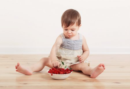little baby eating berry