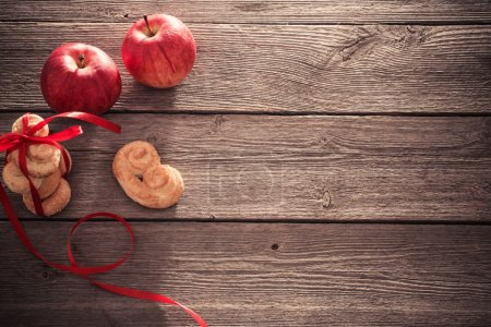 cookies and apples on wooden background