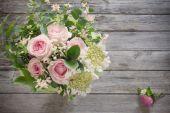 Kytice růží na dřevěný stůl