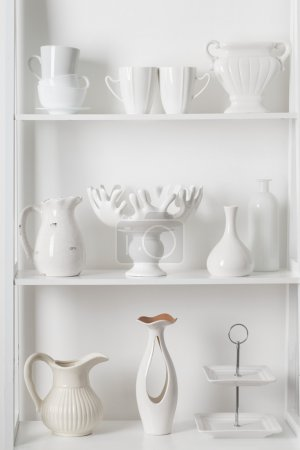Clean dishes and vases on white wooden shelf