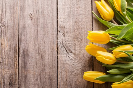 yellow tulips over wooden table background