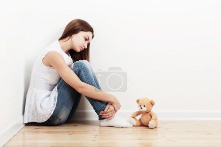 sad teen girl on floor with toy