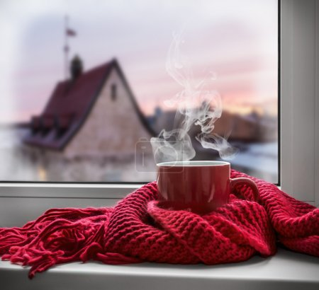 Cup with  scarf on windowsill
