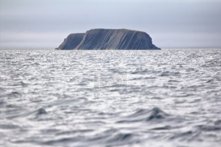 Layered Rock in sea pierced by waves and wind. Arc...