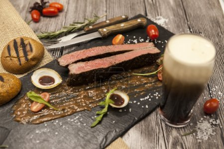 Ribeye steak from marble beef meat with vegetables and barbecue sauce. Served on a plate of black stone with fork and knife and beer
