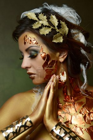 woman with gold-silver bodyart and makeup