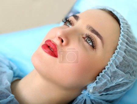 Photo pour Spa sain : Jeune belle femme ayant un maquillage permanent (tatouage) sur ses lèvres. Gros plan - image libre de droit