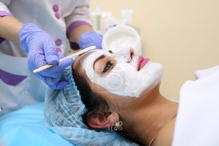 Photo pour Belle femme avec masque facial au salon de beauté - image libre de droit