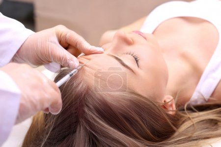 Photo pour Mésothérapie. Belle femme obtient une injection dans son visage . - image libre de droit