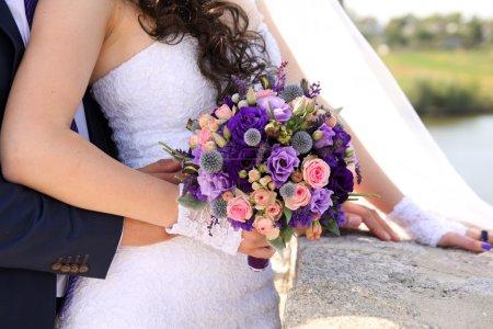Photo pour Mains de la mariée et marié avec des anneaux sur un beau bouquet de mariage - image libre de droit