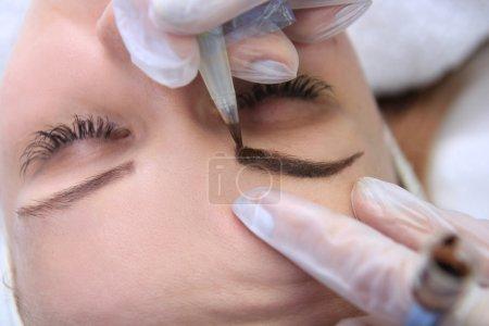 Photo pour Cosmétologue application permanente de maquillage sur le tatouage de sourcils-sourcils - image libre de droit