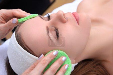 Photo pour Esthéticienne rend nettoyant et exfoliant facial pour belle fille. Salon de beauté. - image libre de droit
