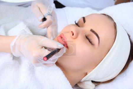 Photo pour Young beautiful woman having permanent make-up (Tattoo) - image libre de droit