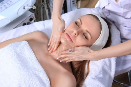 Photo for Young beautiful girl getting spa treatments. Doctor doing massage of the face. - Royalty Free Image