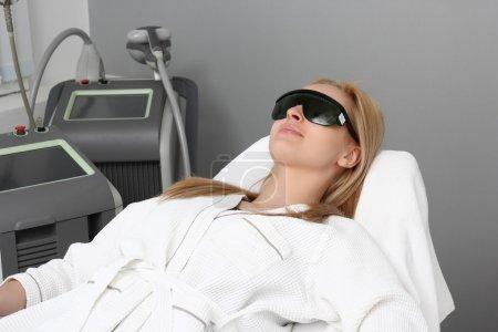 Photo pour Laser épilation dans le salon de beauté. Femme ayant l'épilation du visage. Équipement d'enlèvement de cheveux en arrière-plan au laser. - image libre de droit