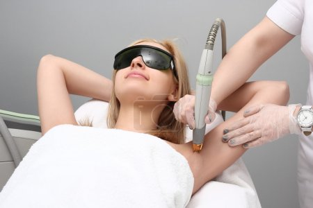 Photo for Blonde woman having underarm Laser hair removal epilation. Laser treatment in cosmetic salon - Royalty Free Image