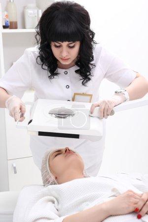 Photo pour Verticale de cosmétologue regardant son client et faisant des procédures professionnelles de cosmétologie dans le salon de spa de beauté sain pour une jeune femme avec la peau fraîche et propre se trouvant sur une table. - image libre de droit