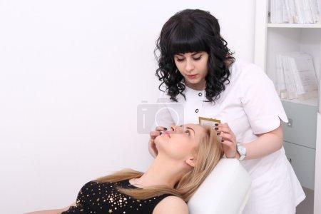 Photo pour Portrait de taille-vers le haut d'une esthéticienne inspectant la peau de son patient, une jeune femme à la peau fraîche et propre regardant sérieusement après une procédure de cosmétologie professionnelle dans un salon de beauté - image libre de droit