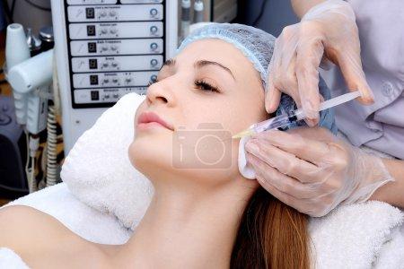 Photo pour Belle femme obtient une injection dans son visage . - image libre de droit