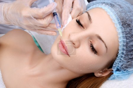 Doctor woman giving botox injections.
