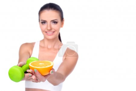 Photo pour Belle athlète brune tenant des haltères et des oranges coupées isolées sur fond blanc . - image libre de droit