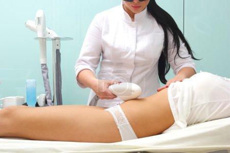 Photo pour Corps de suppression de cheveux au laser. Esthéticienne rend l'épilation du corps de procédure. - image libre de droit